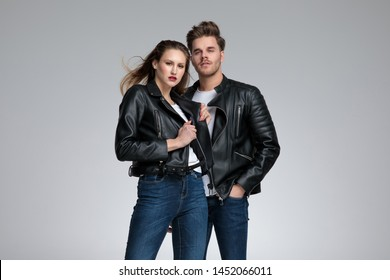 Charming couple posing while she is adjusting her leather jacket and he is holding his hand in his pocket, standing on gray studio background