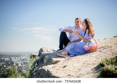 Charming couple sits with glasses of champagne on the rock