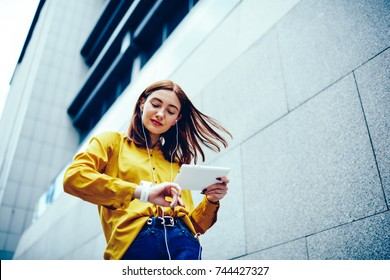 Charming creative female blogger with windy hair checking time on stylish wristwatch while enjoying favorite playlist via earphones.Cute young woman recreating during summer walk with modern device