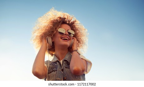 Charming curly blonde listen to music. Young woman with big headphones. outdoors portrait of a trendy girl. Copy space on the right