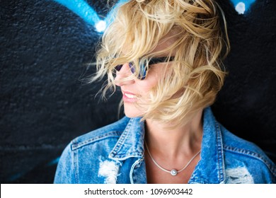 charming curly blonde posing on camera near water on concrete staircase