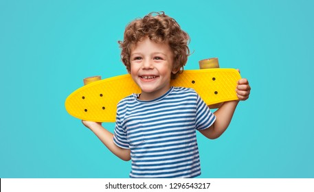 Photo of Charming curly boy holding yellow pennyboard and looking away isolated on aqua blue background.