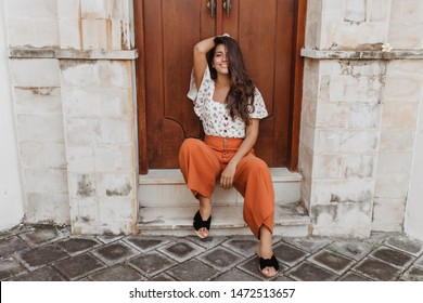 Charming curly brunette woman in culottes and white blouse sits on threshold of house with wooden door