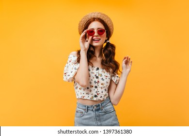 Charming curly girl in stylish cropped blouse and denim skirt wears red sunglasses. Woman in boater looks into camera on orange background