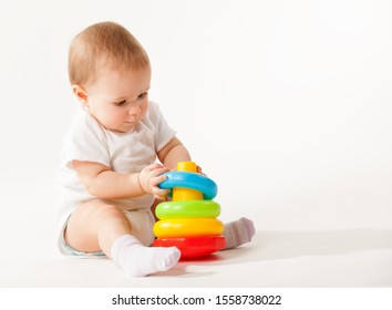 Charming cute baby in white overalls holds rings of a colored plastic pyramid sitting on a white background. Concept of smart and healthy little children concept of child care. Advertising space