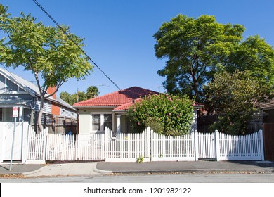 Charming detached bungalow home in the residential suburb of St Kilda, Melbourne with a white picket fence, driveway and red tiled roof.