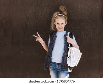 Charming eight-year-old girl in a trendy outfit with a backpack standing on the street on a sunny day