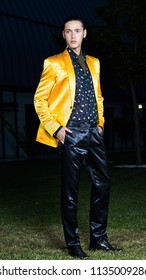 Charming elegant man in yellow jacket standing on green grass. Looking to the camera. Classic style. Studio shot