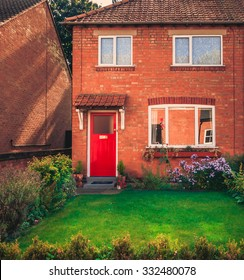 Charming English middle-class home - Red bricked common semi-detached cozy house with red graceful door and front garden at a residential neighborhood in the center of England.