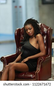 Charming ethnic woman in modern short dress sitting in leather vintage armchair looking alluringly at camera