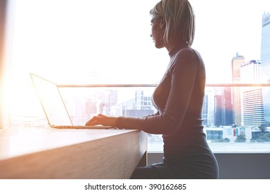 Charming European woman chat in social network via net-book while sitting in modern interior with city scape outside the window, Beautiful young female searching work via internet on laptop computer