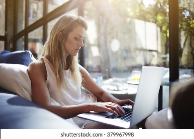 Charming European woman chatting in social network via net-book while sitting in modern interior, beautiful young female searching work via internet on laptop computer during free time in weekend
