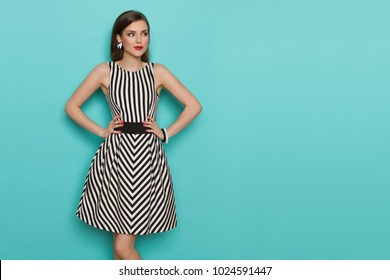 ead7157248b7 Charming fashion model in striped dress posing with hands on hip and  looking away. Three
