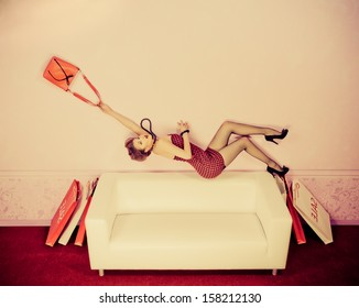 Charming fashionable woman flying over the sofa in the room with her bag. Sepia.