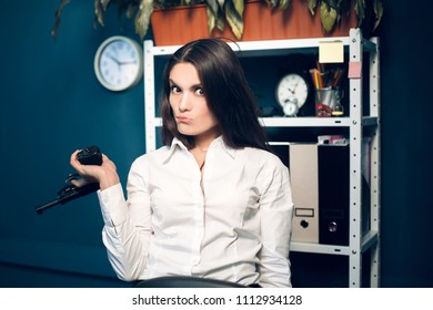 Charming female assistant playing with gun. Cute business lady with funny face expression wearing white shirt carelessly holding gun in her hand pointed to side.