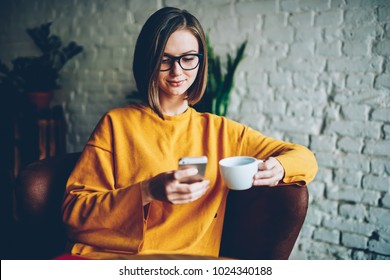 Charming female blogger in eyeglasses updating profile in social network and publishing business post in website on smartphone connected to wireless 4G internet enjoying tasty coffee in leisure time