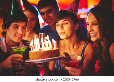 Charming female blowing on candles on birthday cake after making her wish at party