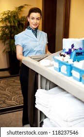 Charming female executive holding toiletries cart and posing in front of camera