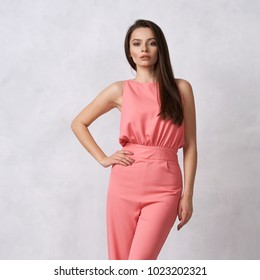 Charming female model with long brunette hair wearing fashionable sleeveless pink jumpsuit and heeled shoes posing against white wall on background. Gorgeous woman dressed in trendy apparel.