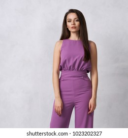 Charming female model with long brunette hair wearing fashionable sleeveless purple jumpsuit and heeled shoes posing against white wall on background. Gorgeous woman dressed in trendy apparel.