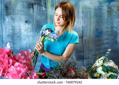 Charming female shop assistant making colorful bouquet with Hydrangea purple, phlox and calla. Flower shop and floristic design master class concept on painted blue wall loft style