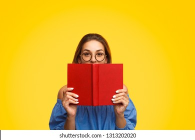 Charming female in stylish glasses looking at camera and hiding half of face behind book with red cover while standing on bright yellow background