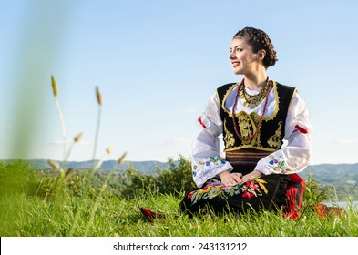 Charming female wearing traditional Serbian clothing and posing outdoors.
