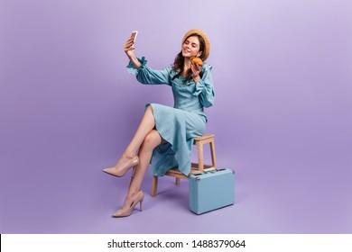 Charming French traveler enjoying crispy croissant sitting on purple background. Girl in straw hat makes selfie