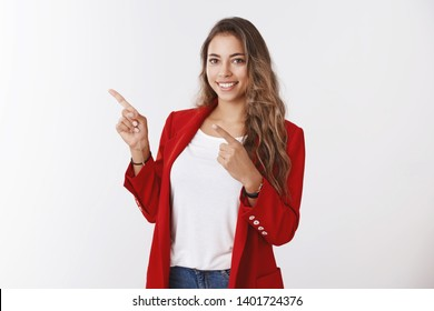 Charming friendly-looking female office worker curly-haired, wearing red jacket, pointing index fingers upper left corner smiling assertive, giving advice showing copy space, grinning confident lucky