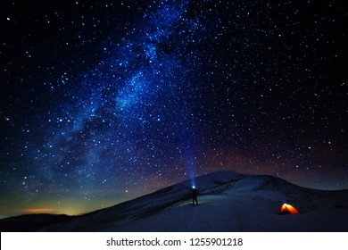 A charming frosty starry night with a fantastic glow of the Milky Way over the snowy peaks of the winter Ukrainian Carpathian Mountains on the background of a tourist with a red tent