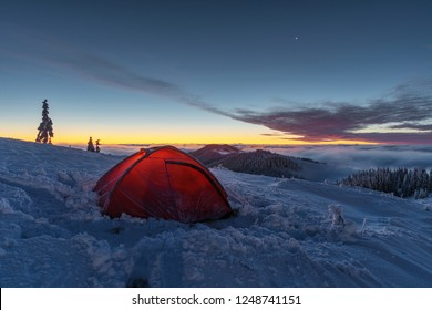 A charming frosty winter dawn in the Ukrainian Carpathians, with foggy sea and snow-capped peaks of the mountains on the background of a tourist red tent