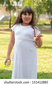Charming full little girl in white dress eating apple outdoor