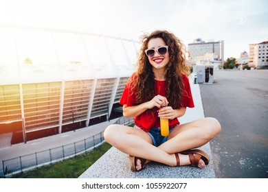 Charming funny young woman in sunglasses sitting on marble slab, holds a bottle of fresh juice. Dressed in red blouse and jeans shorts, with long curly hair. Outdoors.