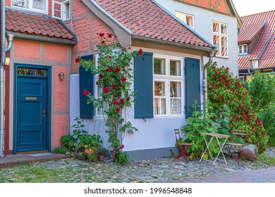 Charming garden with roses,two chairs,table.Old house in the background.Idyllic summer day in countryside.