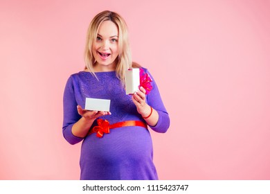 charming and gentle blonde pregnant woman belly ( baby bump ) received a gift in a dress in studio on a pink background . concept of babyshower