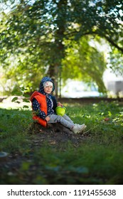 Charming girl 2-3 years old in wood on autumn sunny day, sitting on stump, in blue jacket with a hood and orange down vest, holds a small bark with chestnuts. Full length portrait on a blurred nature