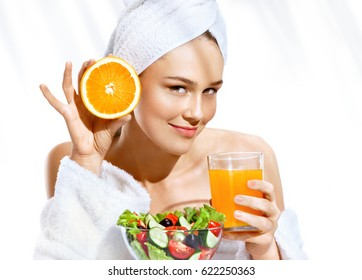 Charming girl after bath enjoying a healthy food. Portrait of smiling woman holding orange juice and orange fruit. Happy and healthy