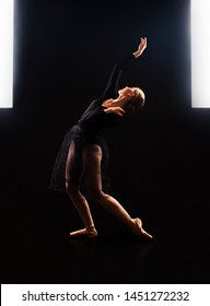 Charming girl ballerina in a black suit, is dancing a ballet in the light of the contour . Shooting a performance on a dark background.