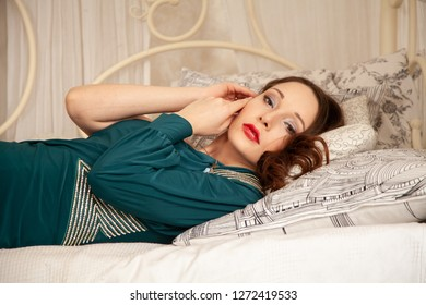 charming girl in a beautiful evening long dress on the background of a canopy bed in