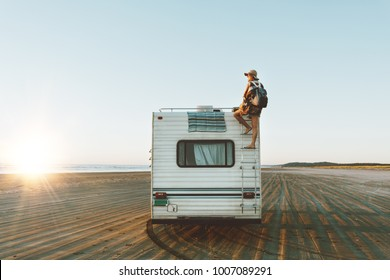 Charming girl with beautiful smile with hat, sunglasses, backpack climing on recreational vehicle on the ocean beach at sunset.