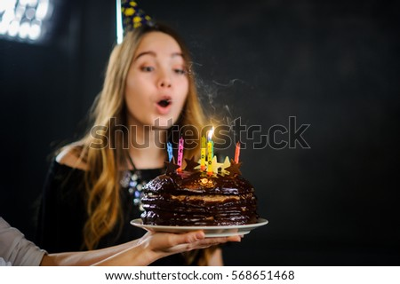 Charming Girl Blows Out The Candles On Birthday Cake Is Elegantly Dressed