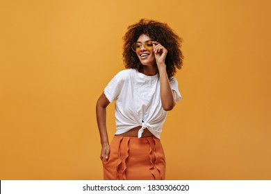Charming girl with fluffy hair in bright sunglasses poses on isolated backdrop. Lady in white t-shirt and orange skirt smiles on yellow background..