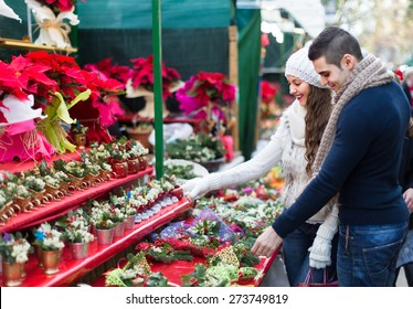 Charming girl with happy  boyfriend choosing red flower at Christmas fair. Focus on girl