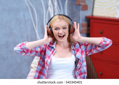 Charming girl with headphones listening to music and singing at home