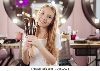 Charming girl holding a set of makeup brushes