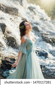 charming girl with light hair in long blue turquoise delicate dress with deep neckline and open shoulders near fast flow of water, birth of mermaid in waterfall in bright light of warm yellow sun