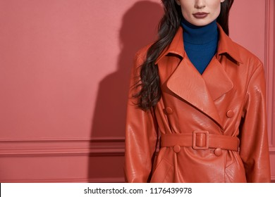 Charming girl is posing on the coral wall background in a studio. She wears a leather orange trench and a blue sweater. Closeup horizontal photo.