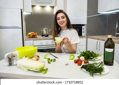 charming girl prepares a salad of different vegetables and greens flavored with olive oil for a healthy lifestyle