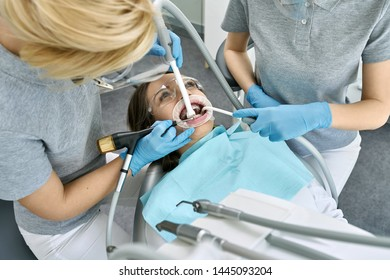 Charming girl in protective glasses with braces and a cheek retractor in a dental clinic. Dentist and her assistant are cleaning her teeth with a help of a water jet and saliva ejectors. Horizontal.