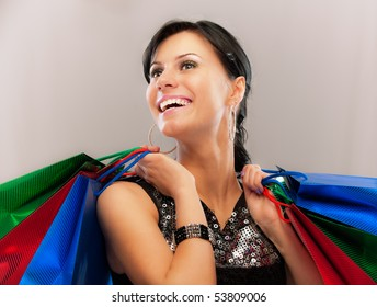 Charming girl with purchases, on gray background.